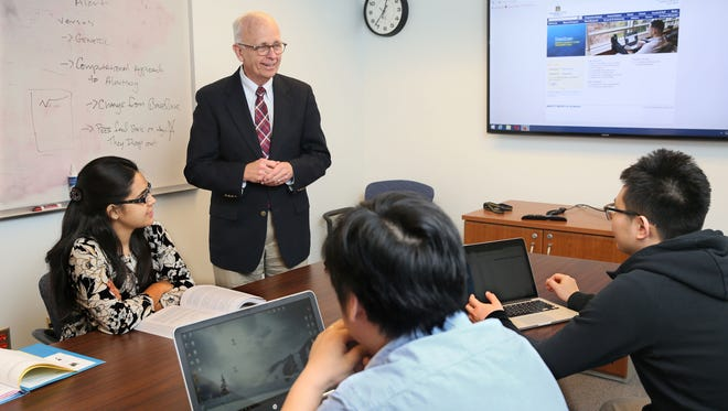 Marquette University professor Thomas Kaczmarek speaks with a group of students in the master's of science computing program. Students are (from left) Badrun Nahar Rumpa, Tao Yan and Duo Zhang.