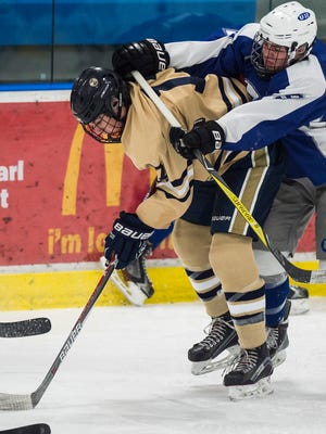 U32 #9 Maxx Perry shoves off Essex #17 Isaac Johnson during their boy's hockey game at Essex on Thursday night, Feb. 1, 2018.
