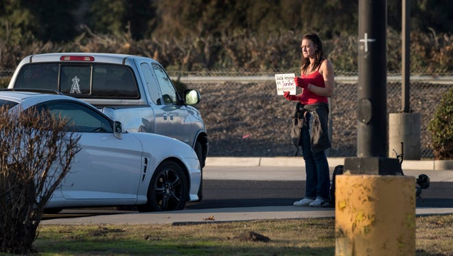 Danielle stands on Noble Avenue hoping for donations from passing motorists on Tuesday, January 23, 2018.