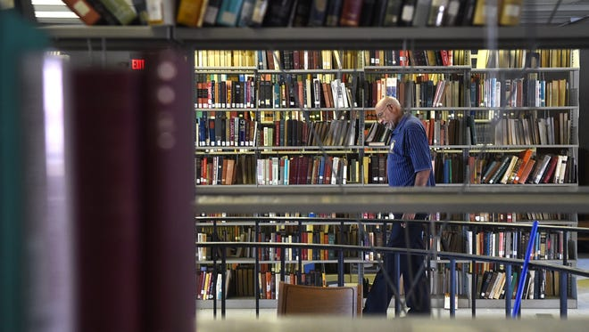 Bob Booker walks through the aisles of Knoxville College's library on Tuesday, Sept. 8, 2015. (ADAM LAU/NEWS SENTINEL)
