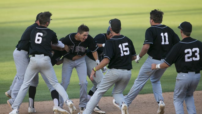 Teammates charge Hamilton's Cole Bellinger (8) as he reacts after scoring a game-winning three-run double in the bottom of the seventh with a full count against Chaparral during the State Baseball Tournament at Maryvale Baseball Park on May 5, 2016 in Phoenix, Ariz.