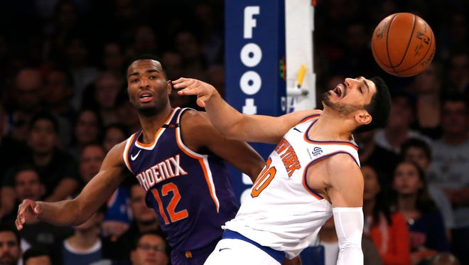 Knicks center Enes Kanter and Suns forward T.J. Warren battle for a rebound during Friday's game in New York.