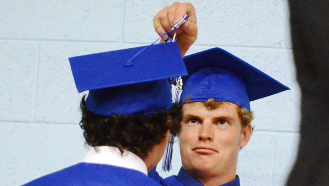 Smith Valley High School senior Monte Stanton moves the tassel to the other side of the cap, symbolizing they've graduated, for a fellow graduate after they've crossed the stage during Friday's commencement.