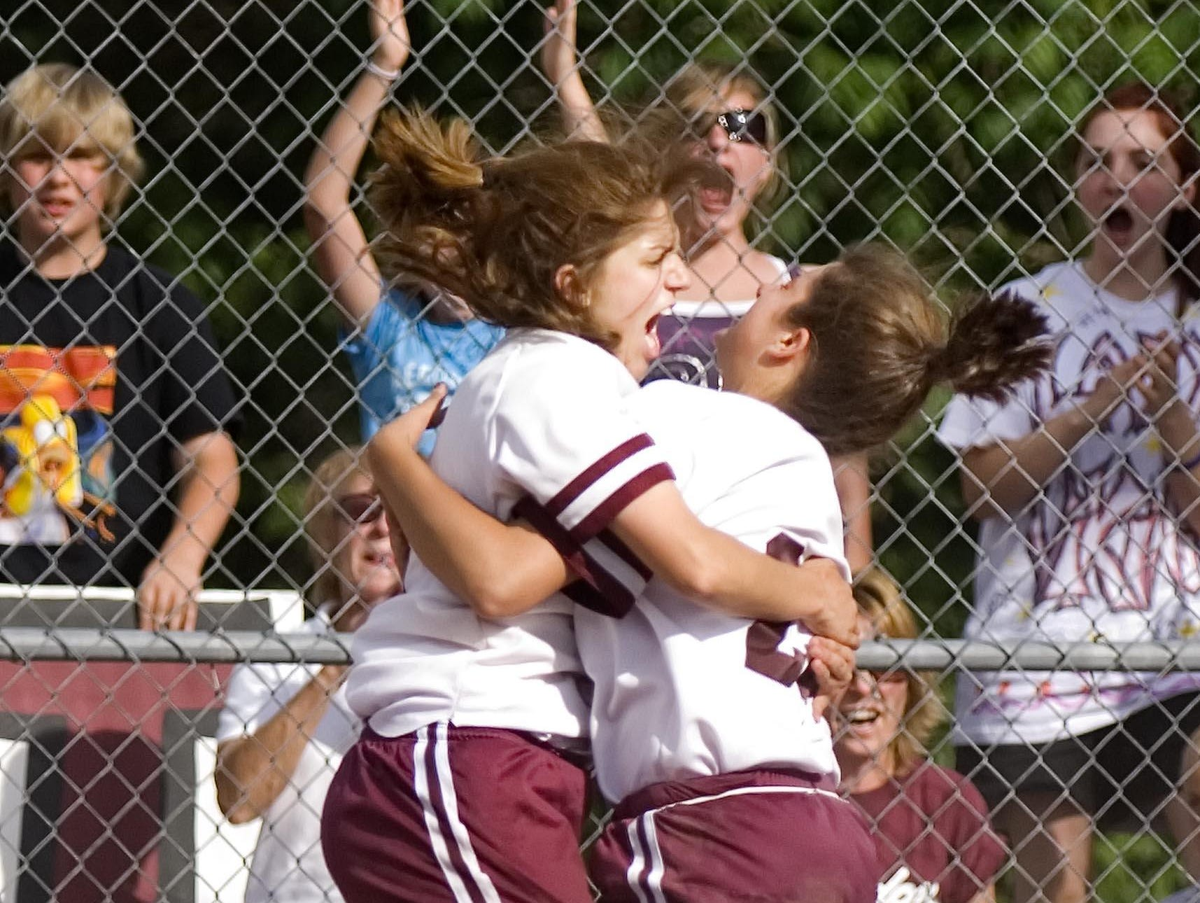 Lyndon Institute's Margaret Hilton (left) and Shauna Poole celebrate after Poole scored the go-ahead run in the 9th inning to defeat Harwood Union High School in the Division 2 state softball championships in Poultney on Friday June 13, 2008. (GLENN RUSSELL, Free Press)