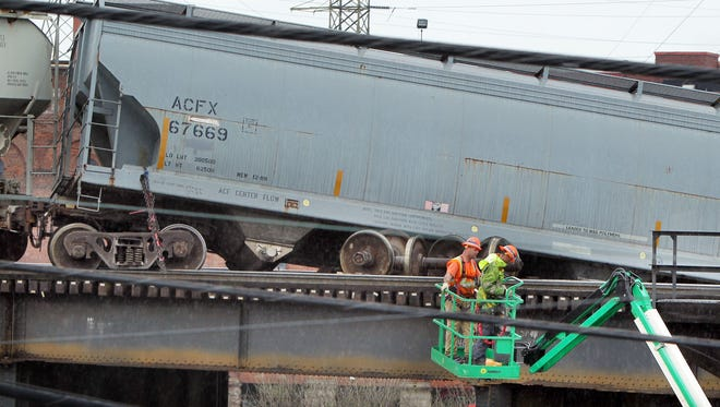 Workers in a check the derailed train cars on elevated tracks along W. Third Street just west of Downtown. Neither of the derailed cars has been secured to a crane as of 11:50 a.m.