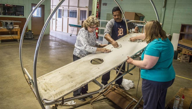 Linda Holderbaum, Doug Sturdivant and Kimber Thompson clean up a bed made by Styrker Inc. at the Battle Creek Regional History Museum. The new museum will be open today and next weekend.