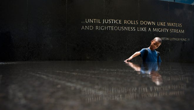 Benjamin Levett, 6, runs his hands through the Civil Rights Memorial fountain during a memorial to honor civil rights leader Julian Bond held by the Southern Poverty Law Center on Saturday, Aug. 22, 2015 in Montgomery, Ala.