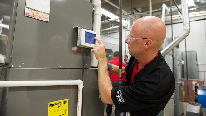 Trainee Scott Merrill of Brockport looks over a furnace during a boot camp training at Isaac Heating & Air Conditioning in Rochester.