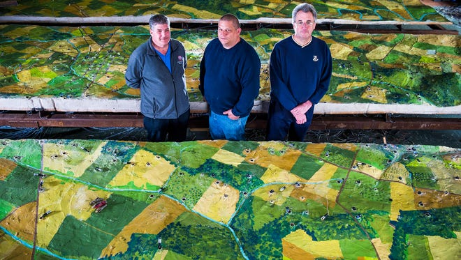 From left, Ernie Lawson, Greg Ruff and Scott Roland pose for a photograph with the four pieces of the electric map of the Battle of Gettysburg.  Roland acquired the piece from a government auction in 2012 for over $14,000. Ruff, an electrician, has been working on helping Roland wire the 632 lights that are part of the map and Lawson, a computer programer, is designing a computer program that will run the narration, lights and show.