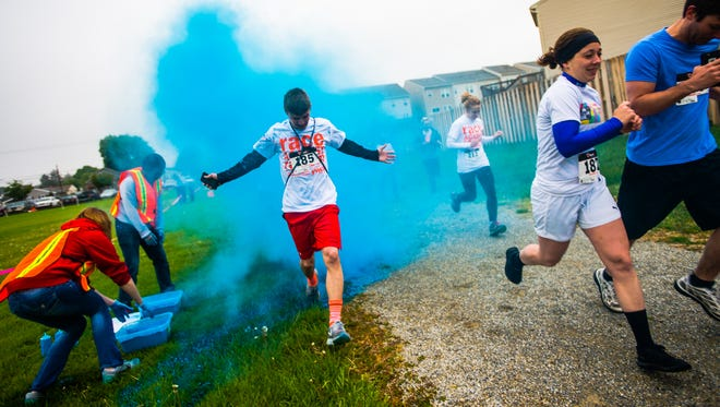 Tanner Fuhrman runs through a cloud of blue hued starch powder during the second annual Hanover YWCA Race Against Racism color run at Moul Field on Saturday morning April 30, 2016 in Hanover.