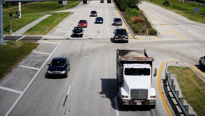 A truck is seen hauling sand in October 2013 on Corkscrew Road crossing under I-75 in Estero. Heavy traffic has been a concern for residents with dump trucks hauling the natural resource to renourish beaches in Naples.