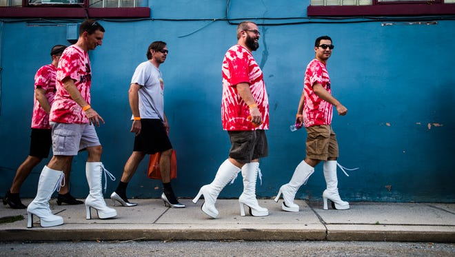 Men wearing platform shoes traverse Middle Street in Hanover in August during the Walk a Mile in Her Shoes event that helps benefit the Hanover YWCA Safe Home and Still Waters programs. Issues of women and sexual assault have been in the news after comments made  by presidential candidate Donald Trump came to light recently.