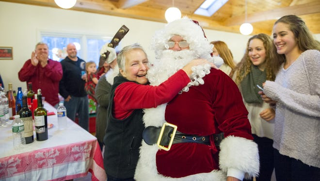 """Kathy Haight hugs """"Santa,"""" upon his arrival at the Camp Eastman lodge the Haight family has rented every Christmas season to celebrate the holiday."""