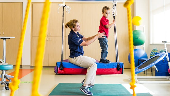 Claire Le Boulenge, left, works with Ace Tidwell, 4, at the rehabilitation center at the new Golisano Children's Hospital Nicklaus Health Center on Thursday, Dec. 22, 2016, in Naples, Fla. Golisano Children's Hospital is finalizing the build-out of a 29,000-square-foot space for the center in Collier County at the northeast intersection of Pine Ridge and Livingston Roads.