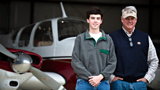 Zack Farmer, 16, and his dad, Jeff Farmer, who is also his flight instructor, stand together on Tuesday, Dec. 20, 2016, in Prattville, Ala.