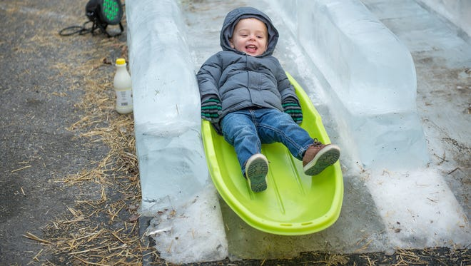 A child slides down the double-wide ice slide during IceFest in downtown Chambersburg in January 2017.