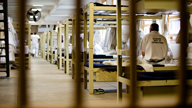 An inmate sits on his bed at Draper Correction Facility in Elmore County, Ala., on Monday, Feb. 6, 2017. Draper Correction Facility is the oldest correction facility in the state of Alabama. The prison opened in 1939. It is currently housing 1059 prisoners, Draper's designed capacity is 656.