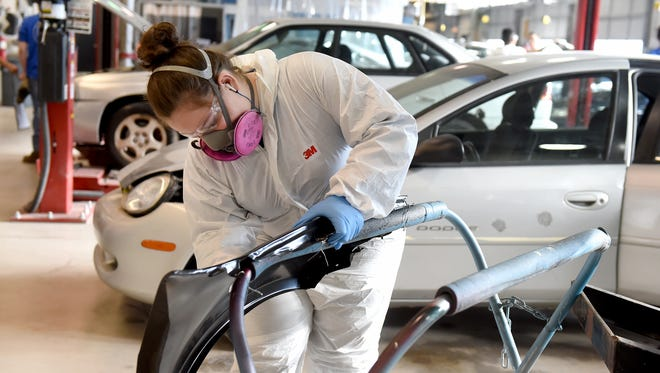 Brianna Rodriguez, a sophomore at York County School of Technology, sands a glaze on a fender in her auto collision class on Friday, Feb. 10, 2017.
