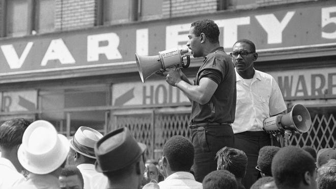 """Congressman John Conyers, Detroit Democrat, uses a bullhorn as he tried to encourage African Americans in Detroit's riot area to go home, July 23, 1967. He was met with shouts of """"No, no."""" As Conyers stepped down a rock hit the street a few feet from him."""