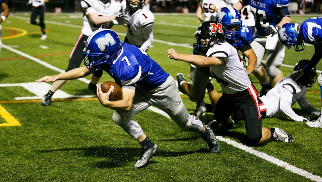 McNary's Robert Benson (7) escapes a tackle from McMinnville on Friday, Oct. 6, 2017, at McNary High School in Keizer, Ore. McNary lost 39-35.