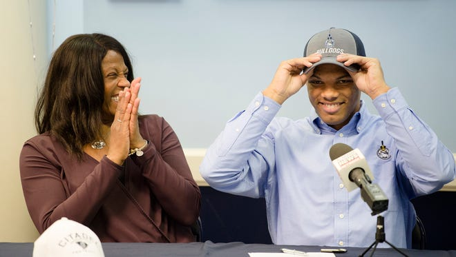 Montgomery Academy's Keefe White puts on a Citadel hat after signing his commitment papers on Wednesday, Feb. 7, 2018, in Montgomery Ala.
