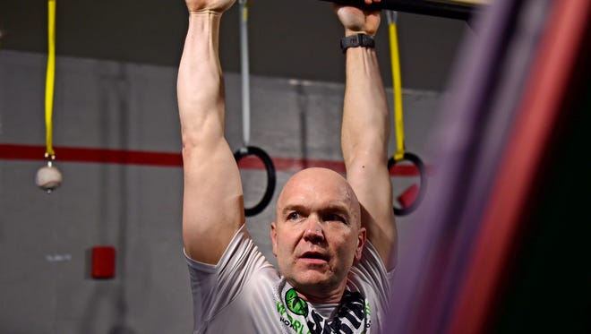 Andy Bell from Fairview Township completes a hang challenge at the end of a Spartan Strong class at Run Higher Training in Lewisberry, Pa. on Tuesday, Feb. 20, 2018. Bell owns Run Higher Training, which is run out of a converted garage at his home. Bell, a teacher at Cedar Cliff high school, lost 100 pounds after starting his fitness journey with a 5K. Now, he's a Boston Marathon qualifier.
