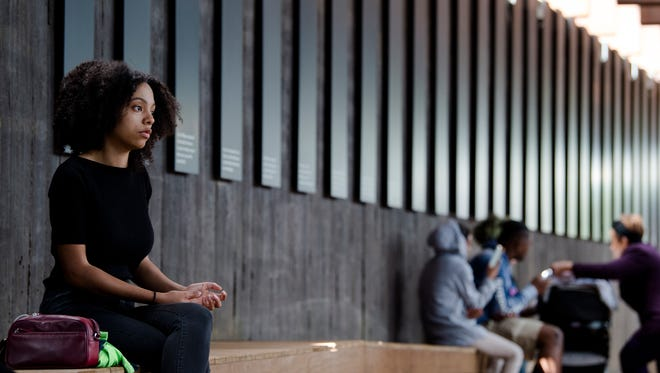 A visitor sits quietly at EJI's National Memorial for Peace and Justice in Montgomery, Ala., on Thursday, April 26, 2018.
