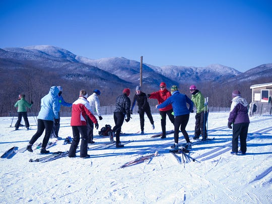 A group of ladies work together on perfecting their form and technique during a women's ski clinic