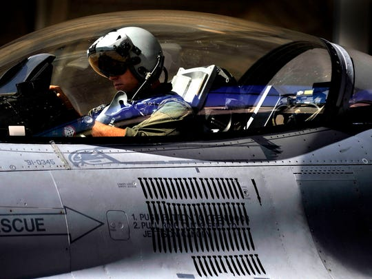 A U.S. Air Force F-16 Fighting Falcon pilot with the 77th Fighter Squadron adjusts in his cockpit before takeoff from Shaw Air Force Base. Holston/Released)