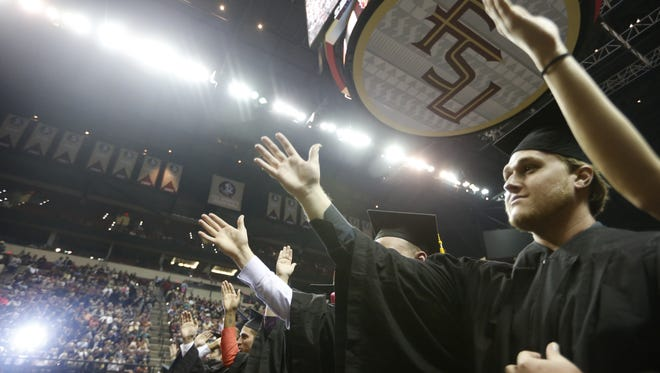 Florida State University students do the tomahawk chop during graduation at the Civic Center .