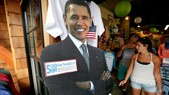 A cut-out photograph of President Barack Obama, center, is positioned near the entrance of a shop, Aug. 6, 2015, in Oak Bluffs, Mass., on the island of Martha's Vineyard.