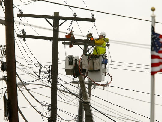 A JCP&L lineman works to repair wires along Main Avenue