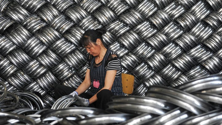 TOPSHOT - A worker checks wheel hubs of baby carriages