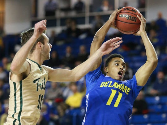 Delaware's Chyree Walker grabs a rebound in front of William and Mary's Connor Burchfield in the first half of the Hens' loss Friday.