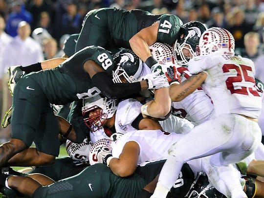 MSU's Kyler Elsworth (41) leaps high above as he,  Shilique Calhoun and the Spartan defense make the game's key stop on  Stanford's Ryan Hewitt to help secure MSU's Rose Bowl victory on Jan. 1, 2014.