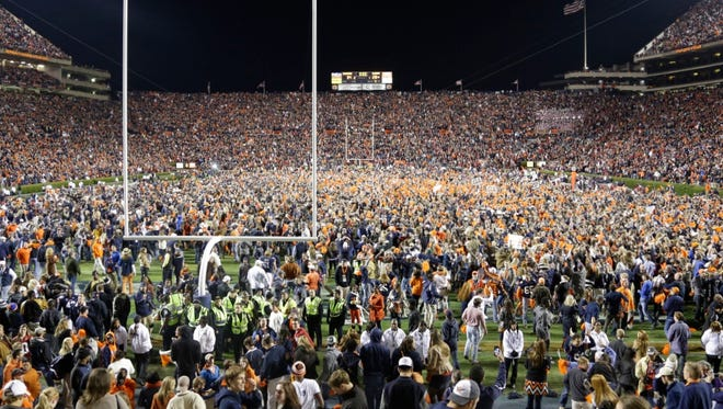 Auburn fans react at the end of a win over Alabama during the second half of an NCAA college football game in Auburn, Ala., Saturday, Nov. 30, 2013. Auburn beat Alabama 34-28.  (AP Photo/Jay Sailors) ORG XMIT: OTKDM
