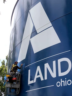 Nike Bunjnj of L&D Painting out of Michigan paints the City of Ashland logo on the water tower at the corner of Mifflin and Claremont Avenues on Sunday as the water tower restoration project continues.