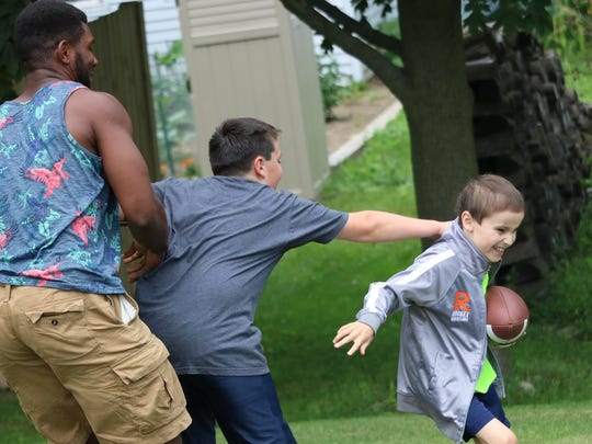 From left: Michael Esiobu, Jon Deppiesse and Mason Deppiesse play a game of backyard football in Cedar Grove on July 13, 2016. Esiobu befriended the brothers following Mason's cancer diagnosis last year and has provided them with support and fun through the ups and downs of Mason's journey.