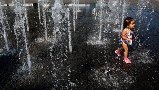 Ivy Lynn Thomas, 1, runs through a spray pad at Smale Riverfront Park on Monday, June 18, 2018 in Cincinnati.