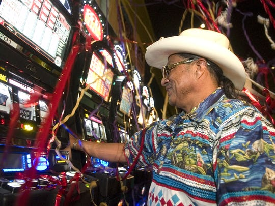 "As strings of confetti fall around him, Mitchell Cypress, chairman of the Seminole Tribe of Florida Tribal Council, ceremonially participates in the ""first pull"" on one of the new recently installed Vegas Style slot machines at the Seminole Casino in Immokalee, Fla., on June 12, 2008."
