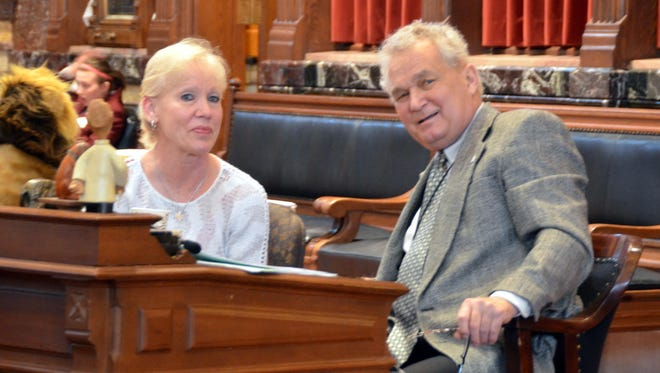 Mary Kresser, left, friend and legislative clerk for Sen. Joe Seng, D-Davenport, right, chat on the Iowa Senate floor on Friday morning. She has been at his side throughout the session as he has battled brain cancer. Both were honored by the Senate Democratic Caucus on Friday morning.