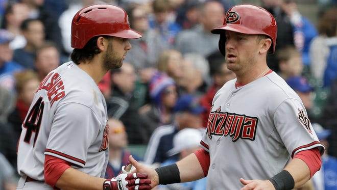 Diamondbacks' Cliff Pennington, right, celebrates with Mike Bolsinger after scoring on a double hit by Tony Campana  during the second inning of a baseball game against the Chicago Cubs in Chicago, Thursday, April 24, 2014.
