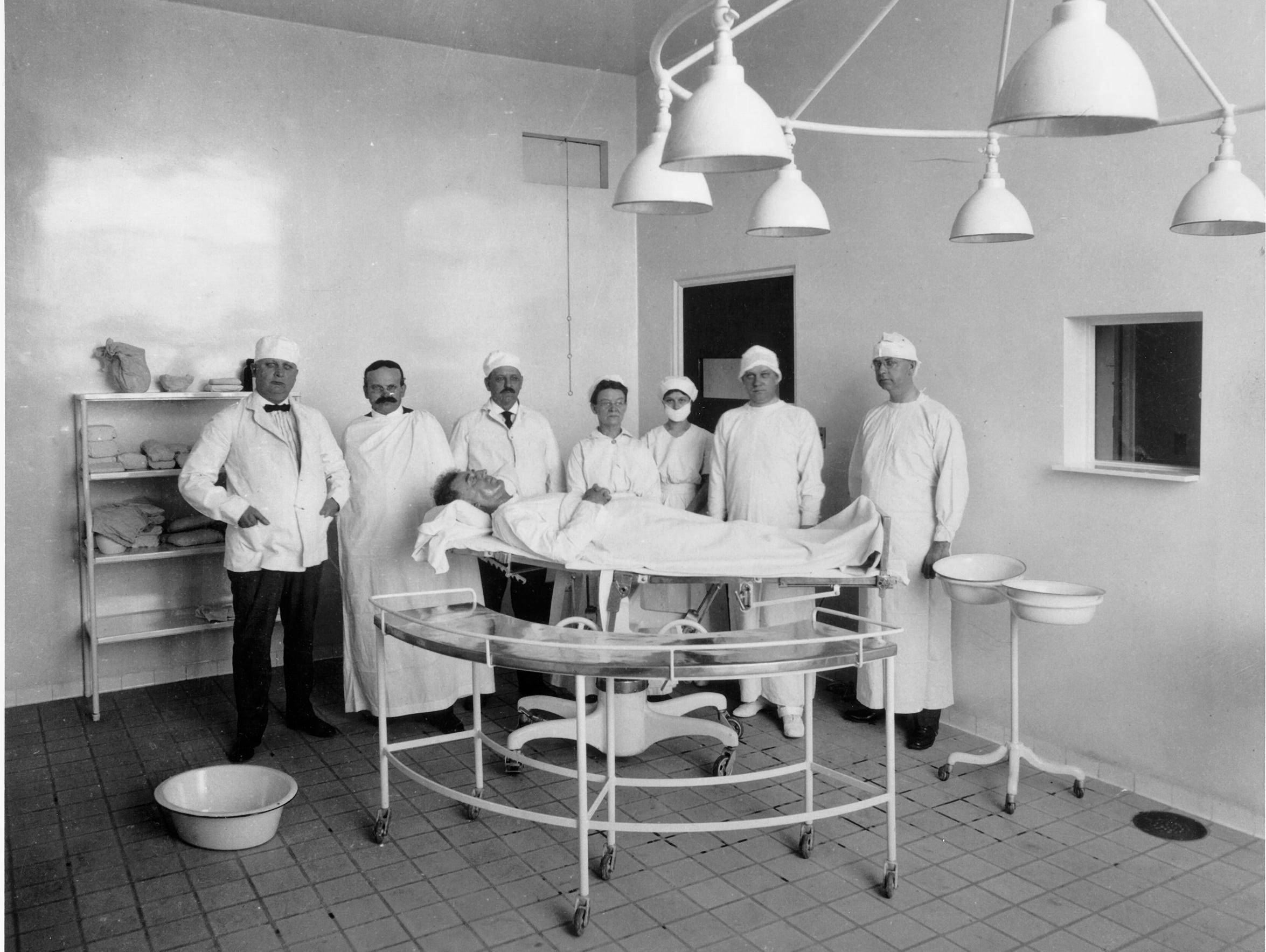 A group of surgeons prepare for surgery in the early