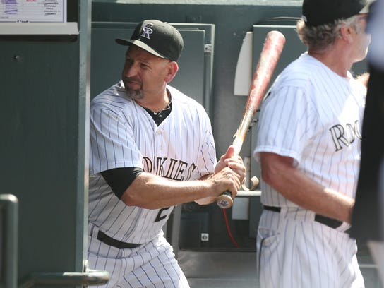 Upset after being ejected from the game, Colorado Rockies manager Walt Weiss takes a bat and smashes it into the wall by the batting rack in his team's dugout on his way to the showers against the Atlanta Braves in the eighth inning of the Rockies' 10-3 victory in a baseball game in Denver on Thursday, June 12, 2014. Weiss was upset over the Rockies' Corey Dickerson being hit by a pitch thrown by Braves relif pitcher David Carpenter. (AP Photo/David Zalubowski)