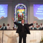 Reverend Roger Peterson leads visitors to the First Presbyterian Church of Fort Myers in song during the 27th Annual Mrs. Edison's Hymn Sing on Tuesday.  The event was sponsored by the Galloway Family of Dealerships and is part of the Edison Festival of Light to benefit the Soup Kitchen of CCMI.
