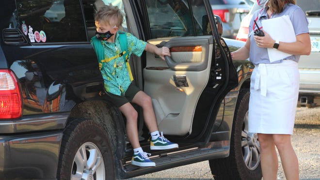 Valerie Crabtree, principal at Northwest Heights Elementary in Durant, opens a car door for a student on Aug. 24.