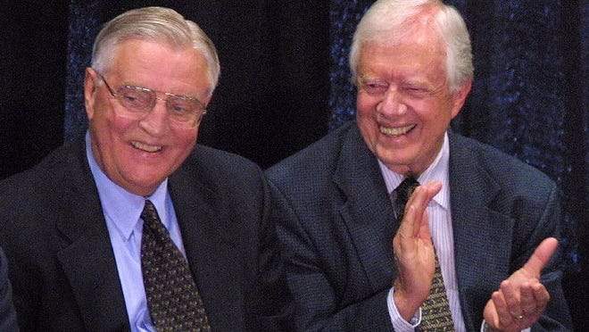 Former president Jimmy Carter, right, claps for his former vice president Walter Mondale, left, at a ceremony held to dedicate a hall named in Mondale's honor at the University of Minnesota Law School in Minneapolis on May 17, 2001.
