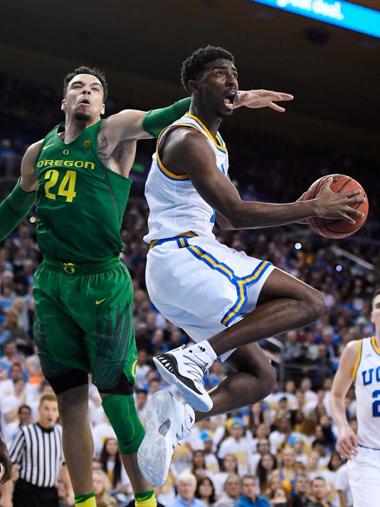 UCLA guard Isaac Hamilton, right, shoots as Oregon forward Dillon Brooks defends during the second half of an NCAA college basketball game, Thursday, Feb. 9, 2017, in Los Angeles. UCLA won 82-79. (AP Photo/Mark J. Terrill)