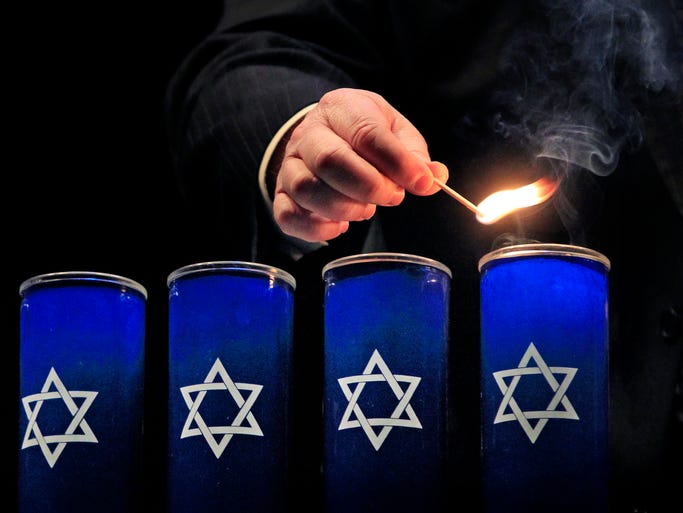 Rabbi Benjamin Sendrow of Congregation Shaarey Tefilla lights six candles at Carmel's 2014 Days of Remembrance ceremony in memory of the six million lives extinguished in the Holocaust during a noon ceremony at the Tarkington Theater on Friday, May 2, 2014.
