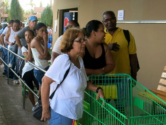 People wait in line outside a grocery store to buy
